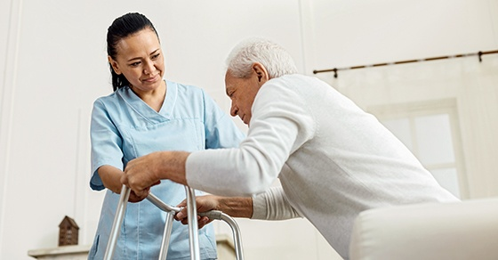 old man and walker with healthcare worker